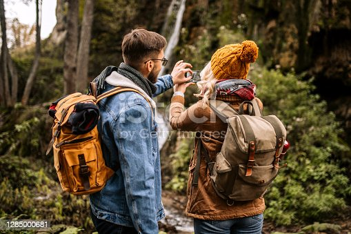 Rear view of young hiking couple with backpacks standing in a front of small forest waterfall, taking a photo