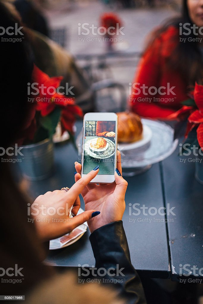 Photographing dish at the restaurant with friends stock photo