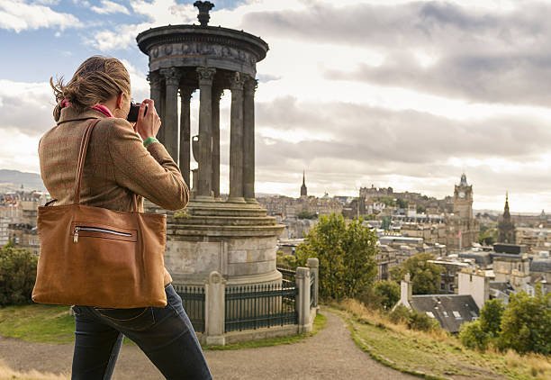 Photographing Edinburgh A woman taking a photograph of Edinburgh's skyline from Calton Hill, with the 19th Century Dugald Stewart Monument in the foreground. edinburgh scotland stock pictures, royalty-free photos & images