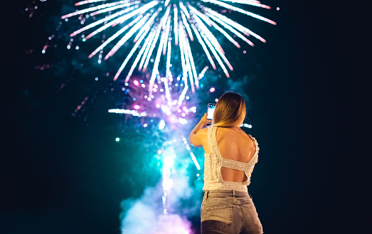 Young woman is admiring and photographing fireworks on the night sky