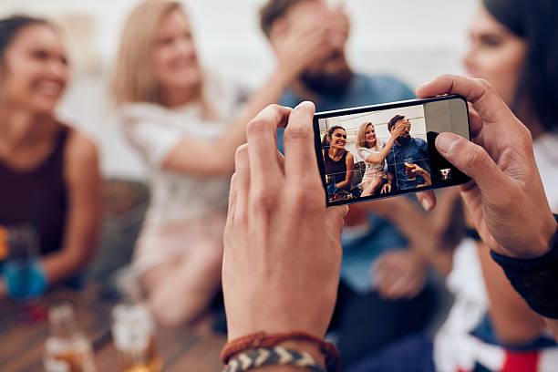 fotografieren freunden auf party mit handy - dachschräge einrichten stock-fotos und bilder