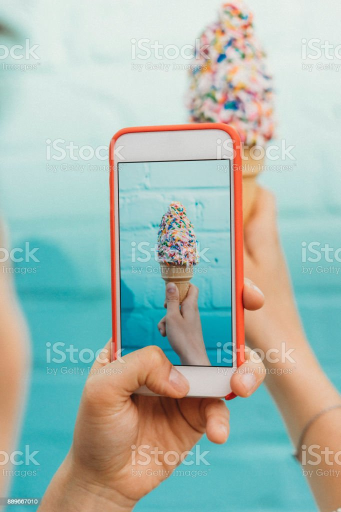 Photographing ice cream against blue wall stock photo