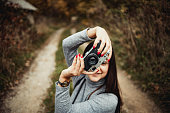 Young woman photographing the autumn season - Woman in the woods during warm color fall