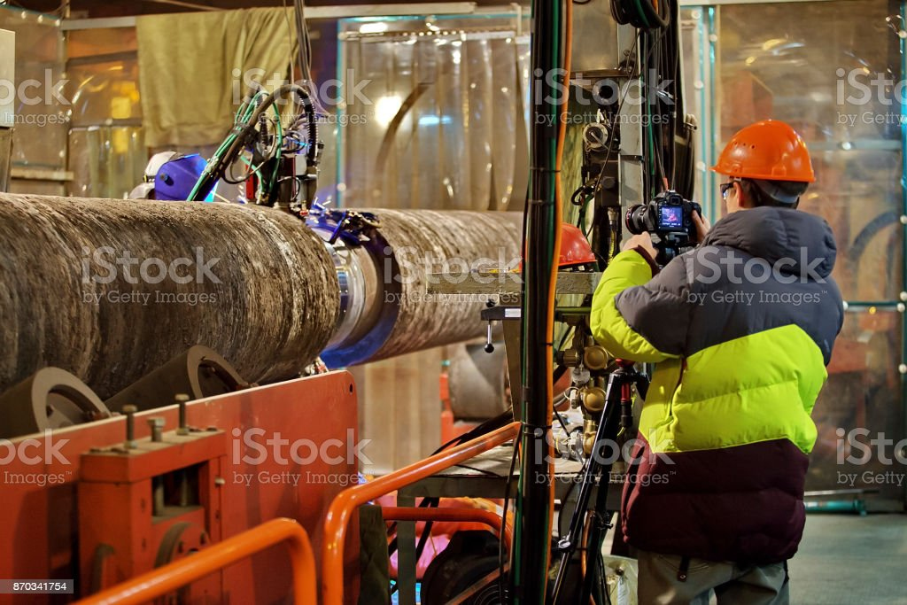 Photographing of welding of the pipeline in shop stock photo