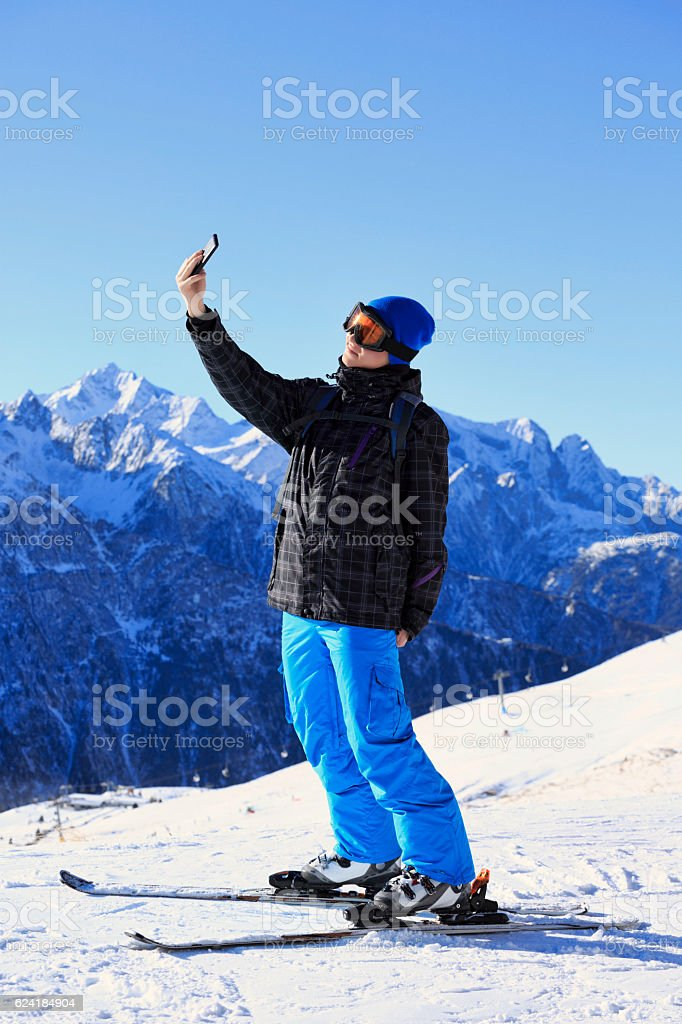 Photographing  Snow skier teenage boy taking selfie photo  Alps mountain stock photo