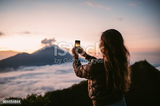 One woman, standing high on beautiful mountain Batur in sunset alone, photographing sunset with smart phone.