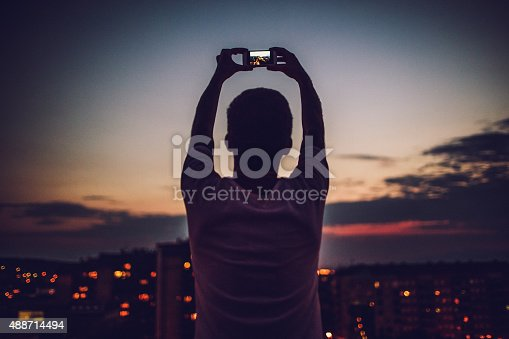 Young man is holding his mobile phone up above his head and capturing that perfect time of the day when sun is going down
