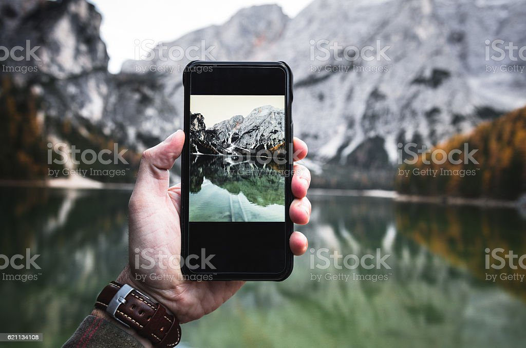Photographing the Braies lake in south tyrol with the smartphone stock photo