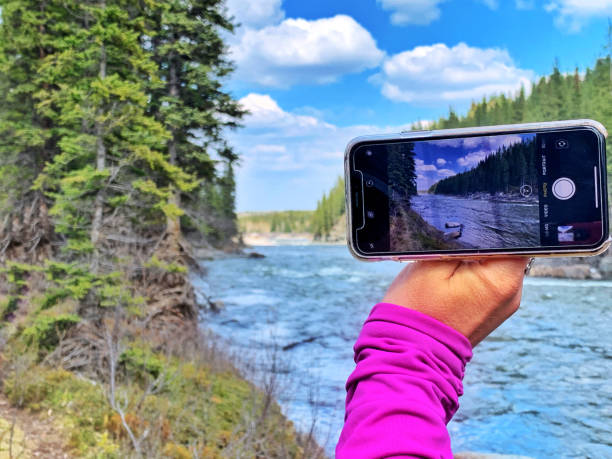 Photographing the Elbow River near Bragg Creek with an iPhone 8 Plus Bragg Creek, Alberta, Canada - May 26, 2019: Close-up of a female hand taking a picture  with an iPhone 8 Plus of the Elbow River in Kananaskis Country. kananaskis country stock pictures, royalty-free photos & images