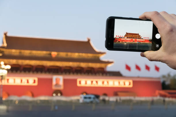 Photographing the Gate of Heavenly Peace at Dusk, Beijing, China Beijing, China - March 13, 2017 - A person takes a picture of the Gate of Heavenly Peace at dusk using a smartphone. The Gate of Heavenly Peace, or Tiananmen, was the former entrance to the Imperial City. mao tse tung stock pictures, royalty-free photos & images