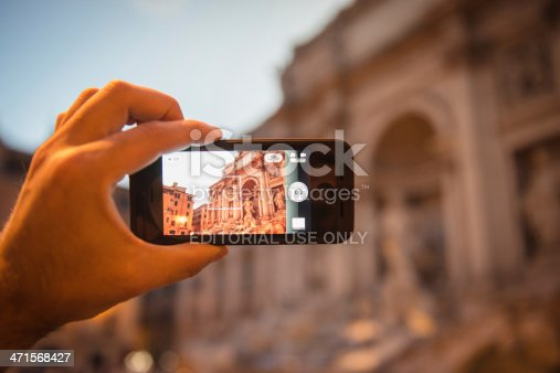Rome, Italy - June 12, 2013: : Man holding the new iPhone 5 and photographing the Trevi Fountain in Rome with his smartphone. The iphone 5 is the new smartphone made by Apple Inc. It was released on September 21st on US and in Uk on 2012, the iPhone 5 is Apple's first mobile phone with a 4