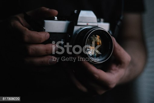 Photographer is holding an old 35mm rangefinder camera, close-up