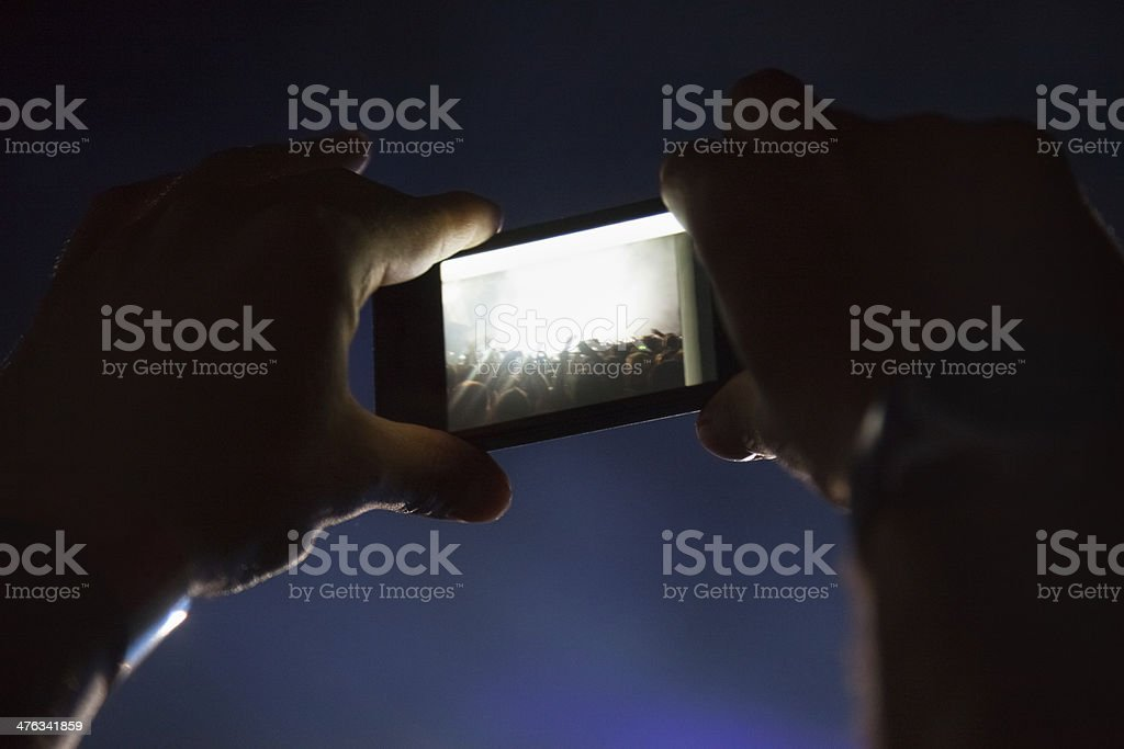 Photographing with cell phone at the concert royalty-free stock photo