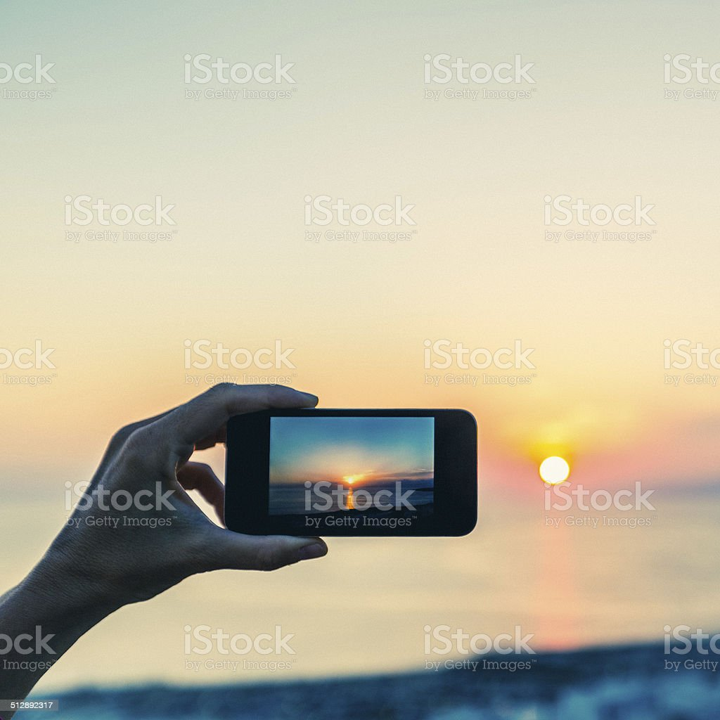 Photographing with smartphone at sunset stock photo