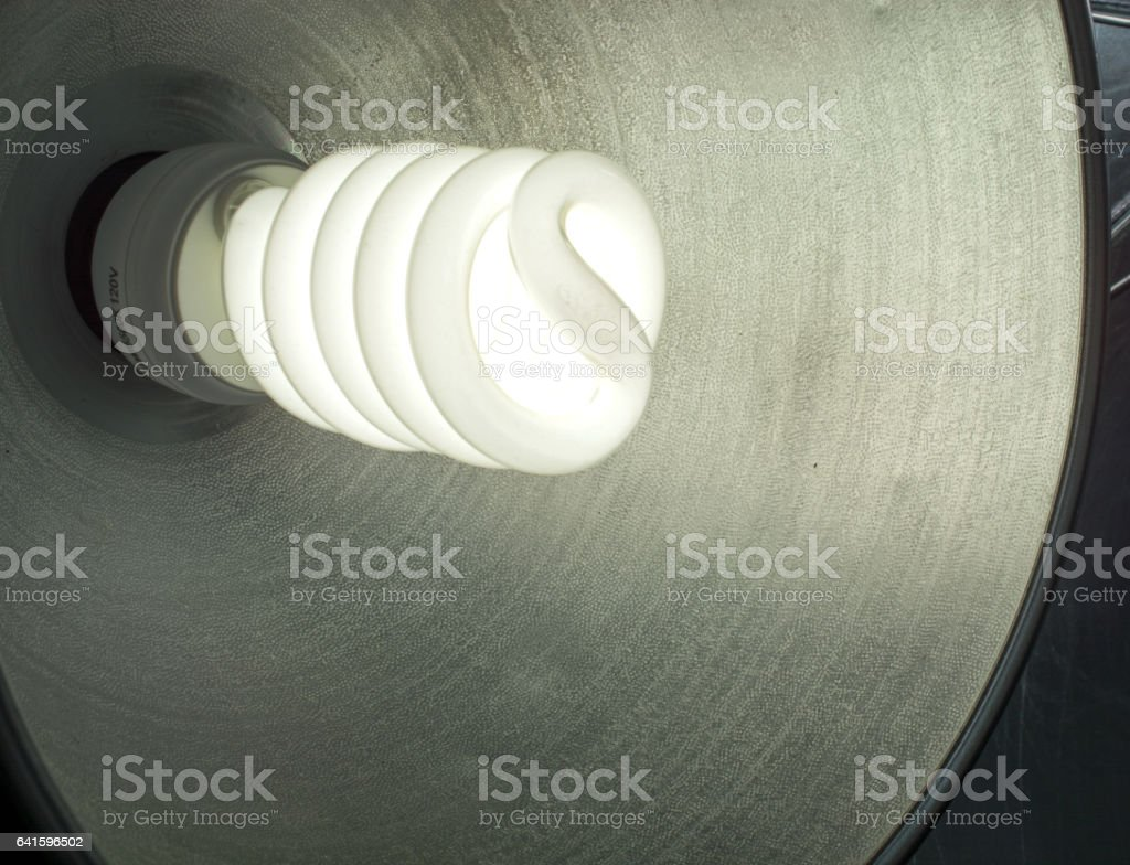 Photography CFL lightbulb illuminated in studio- dimmed stock photo