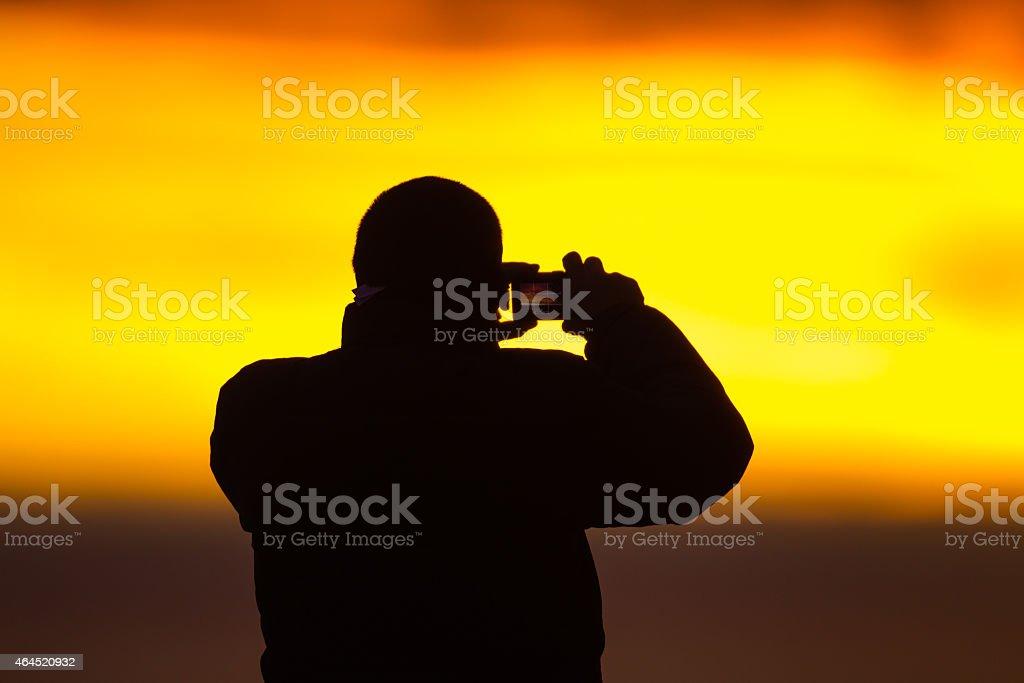 Photogrpher photographs sunrise stock photo