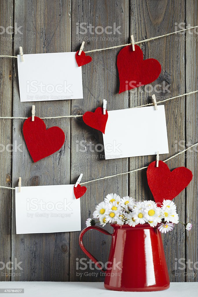 Photos and hearts on wooden wall stock photo