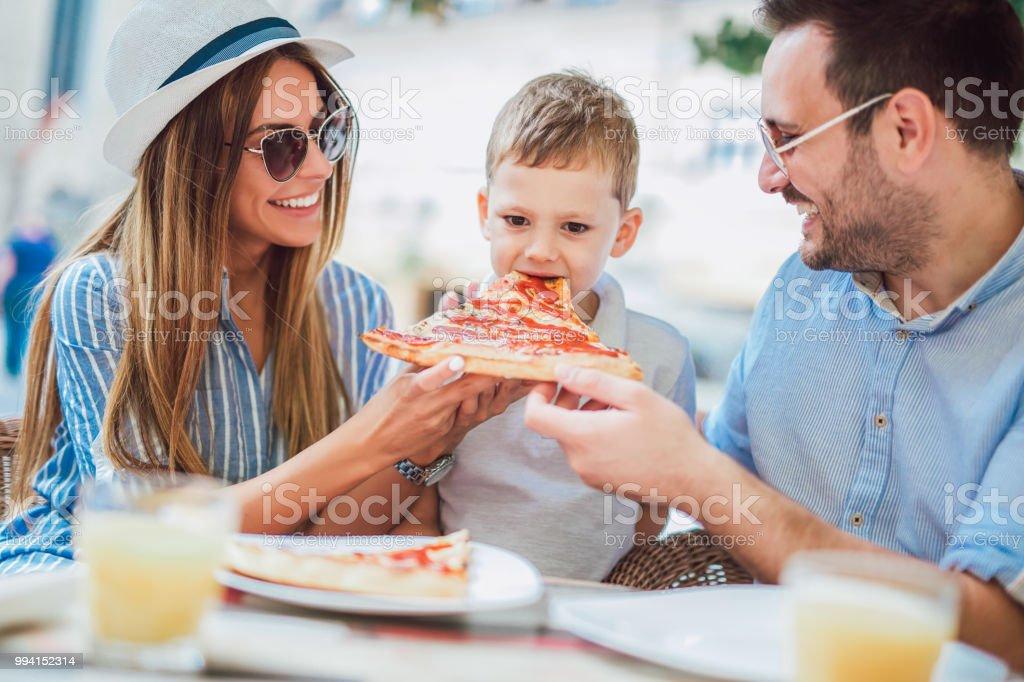 Familia feliz fotos comiendo en un restaurante - foto de stock