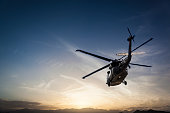 Photos Military Helicopter flying against sunset