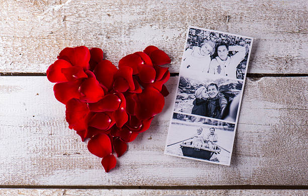 photos of a couple in love. red rose petal heart. - senior valentine stock photos and pictures