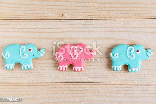 875685464istockphoto Photos of elephants on a wooden background. Children banner. Frame for greeting card newborn boy. Blank for design childish banner with gingerbread. 1127824711