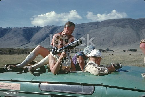 National Park Ngorongoro Crater, Tanzania, 1963. A group of tourists on photo safari in Ngorongoro crater. From the open roof window of the safari buss, participants are taken photos of the African animal world.