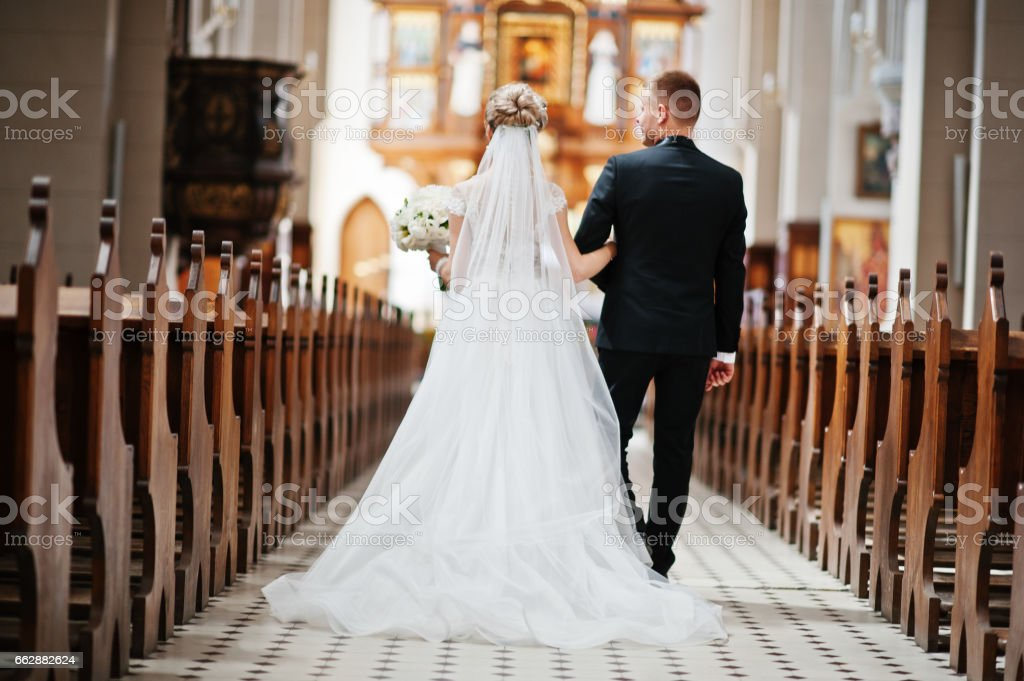 Photosession of stylish wedding couple on catholic church. stock photo
