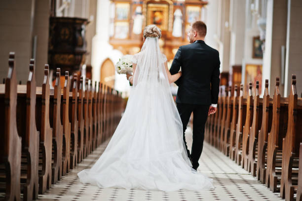 photosession of stylish wedding couple on catholic church. - wedding stock pictures, royalty-free photos & images