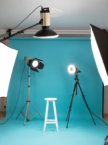 Photo-studio with lighting equipments and blue background paper