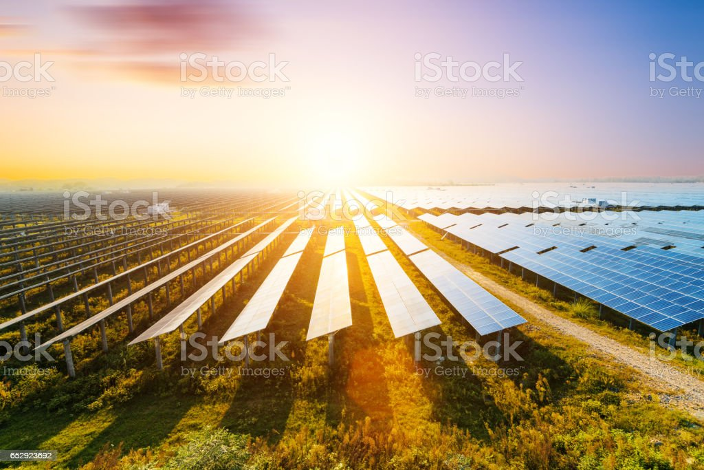 Photovoltaic modules reflect sunset light and clouds stock photo