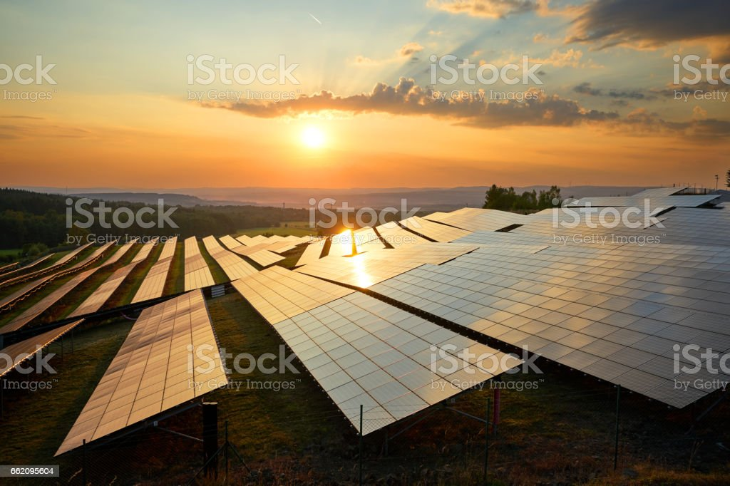 Photovoltaic panels of solar power station at sunset. stock photo