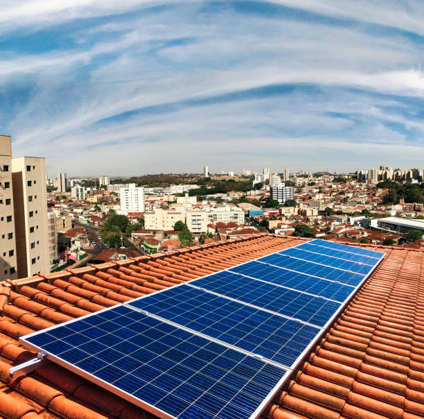 photovoltaic power plant on the roof of a residential building on sunny day - solar panel imagens e fotografias de stock
