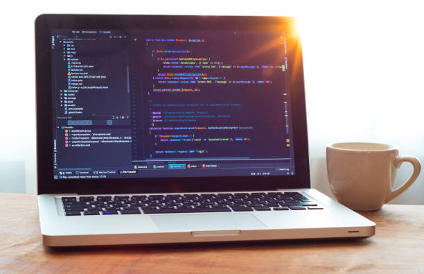 Php code on laptop (web developing) and white mug in sunlight stock photo