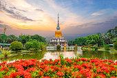 Mahasarakham Thailand - 2018 September 21: Phra That Na Dun pagoda Thailand with red flower and beautiful sky sunset stupa that buddhism worship and landmark of Maha sarakham Province
