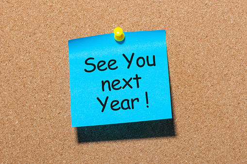 phrase See you next year pinned at cork board.