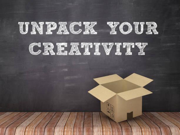 desembale su creatividad frase con caja de cartón en piso de madera-fondo de pizarra-renderizado 3d - suministros escolares fotografías e imágenes de stock