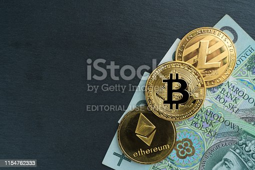Gdansk, Poland - May 22, 2019: Physical Bitcoin, Litecoin and Ethereum gold coins with polish currency (PLN) on a black stone slate plate with chain. Cryptocurrency exchange abstract concept.