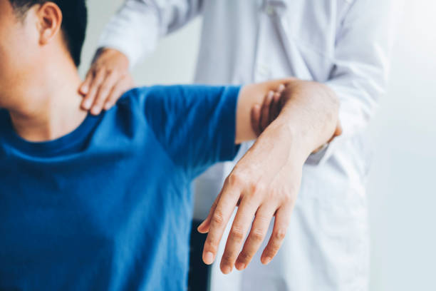 physical doctor consulting with patient about shoulder muscule pain problems physical therapy diagnosing concept - physical therapy zdjęcia i obrazy z banku zdjęć