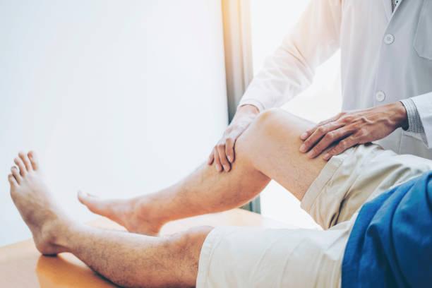 doutor físico que consulta com problemas pacientes do joelho conceito da fisioterapia - articulação humana - fotografias e filmes do acervo