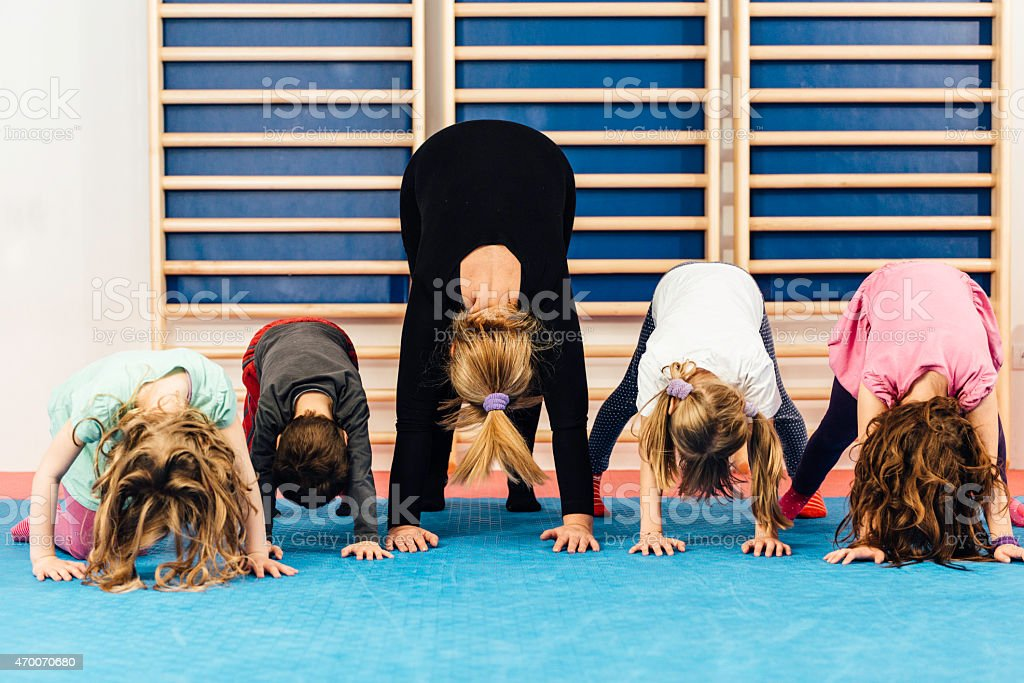 Physical education - Teacher with children exercising stock photo
