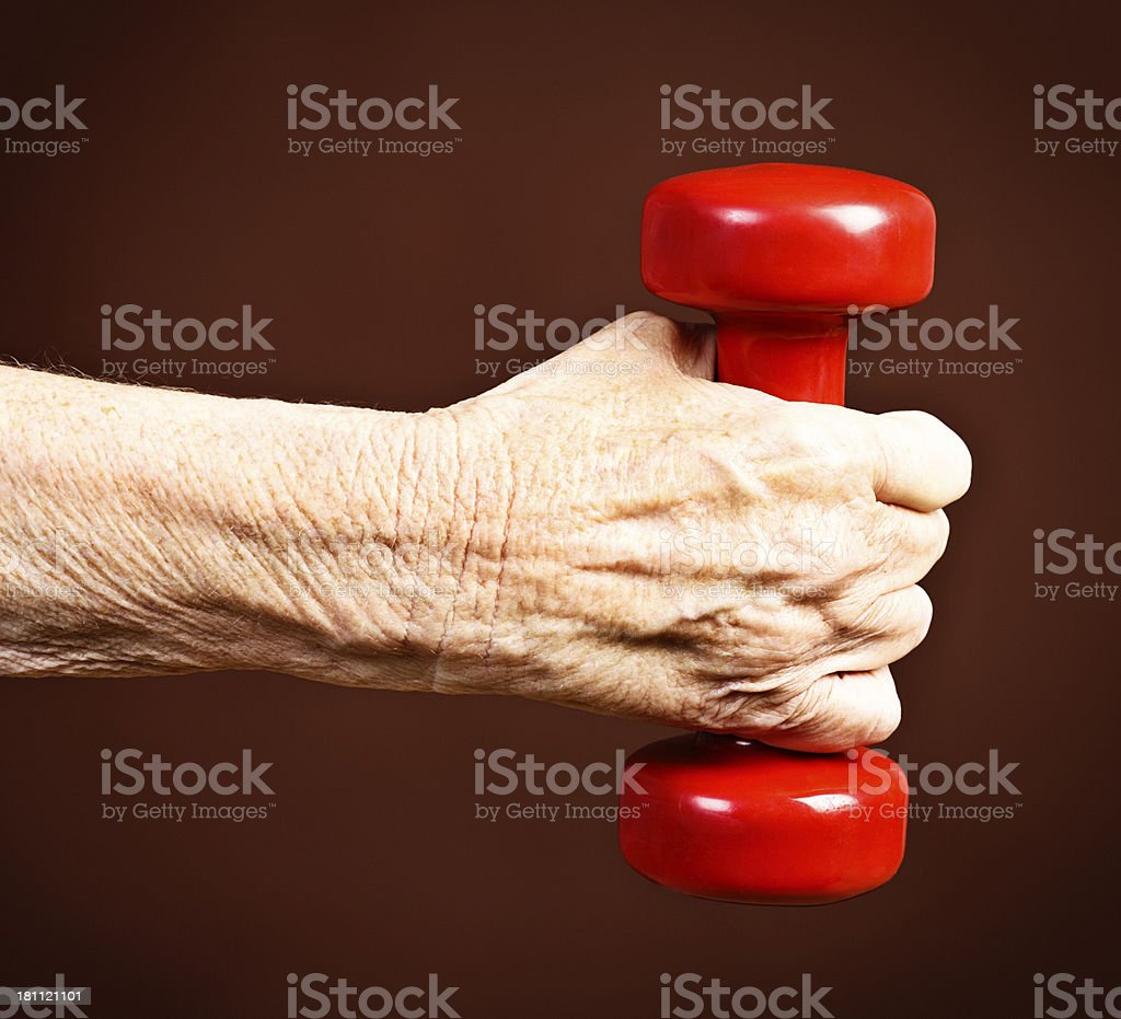 Physical fitness for the aged: wrinkled old arm lifts weight royalty-free stock photo