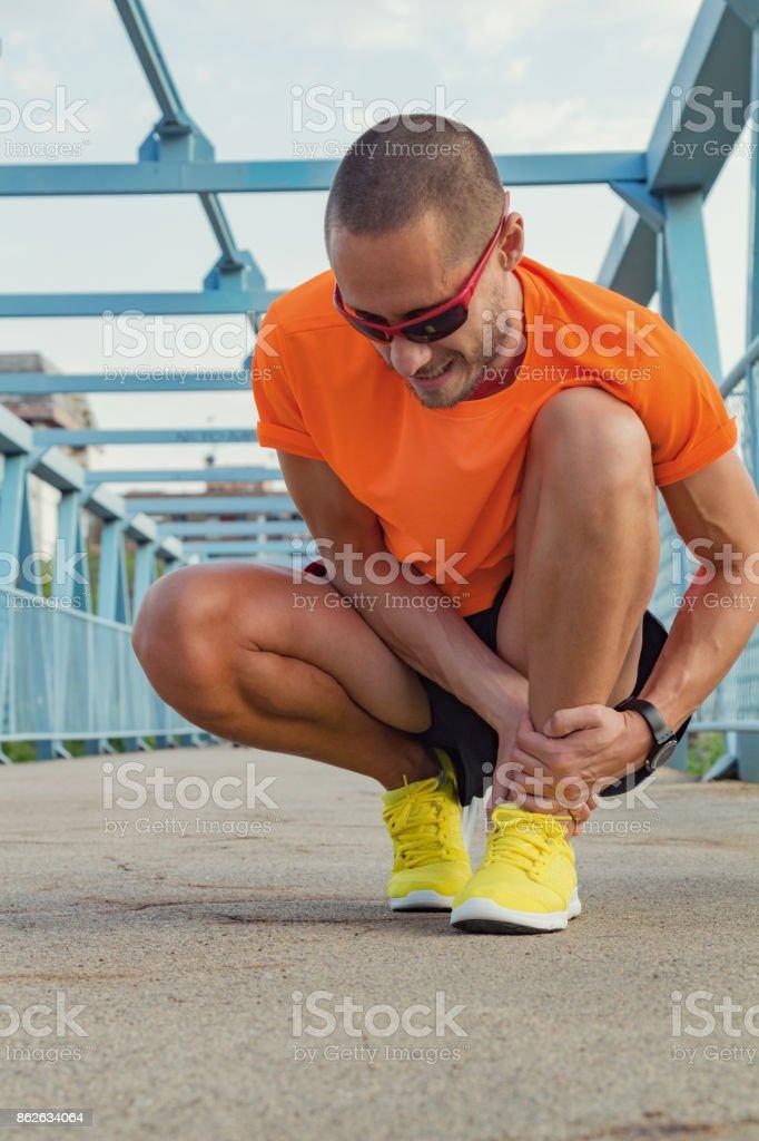 Physical injury during jogging / running / exercising outdoors. stock photo