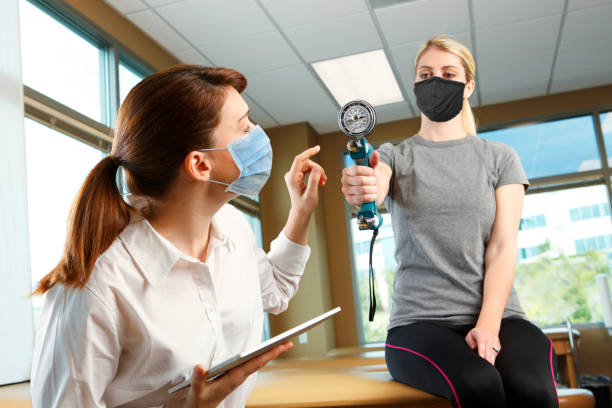 Physical Or Occupational Therapist Wearing Protective Mask Evaluating Grip Strength stock photo