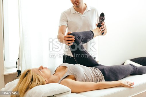 Unrecognizable physiotherapist examining leg injury on a woman lying down.