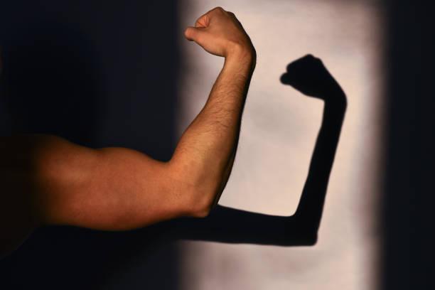 Force physique et faiblesse. La main forte du sportif et sa réflexion sur le mur, une ombre mince. Attendu et réalité. Réalisations sportives et victoire - Photo