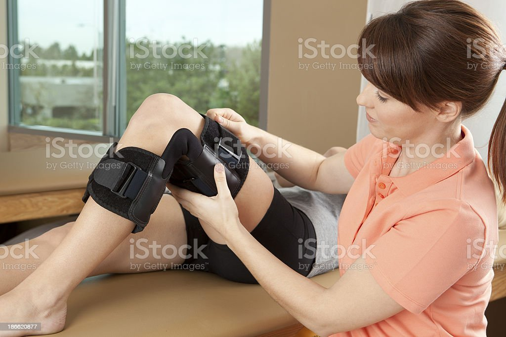 Physical therapist adjusting a knee brace on female patient royalty-free stock photo