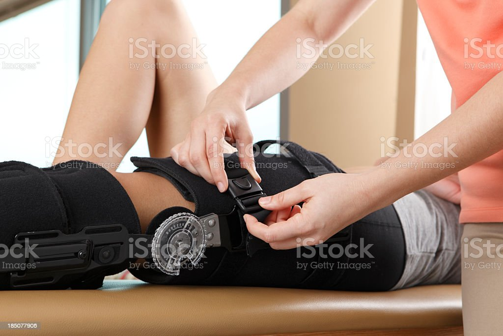 Physical therapist adjusting a knee brace royalty-free stock photo