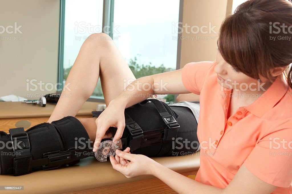 Physical therapist adjusting a knee brace stock photo