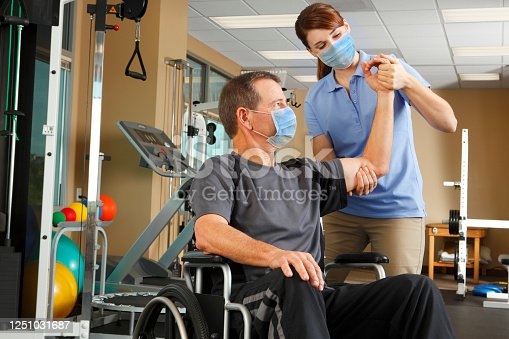 A female physical therapist wearing a protective mask evaluates the range of motion a male patient who also wears a protective mask while sitting in his wheelchair.  The therapist is in her early thirties and the patient is in his mid 50's.  Photographed in a clinical setting with several pieces of exercise equipment in the background.