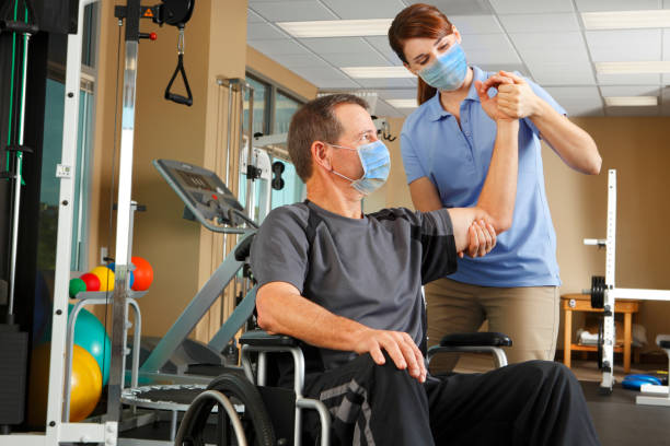 Physical Therapist And Patient In Wheelchair Wearing Protective Masks While Therapist Evaluates Range Of Motion A female physical therapist wearing a protective mask evaluates the range of motion a male patient who also wears a protective mask while sitting in his wheelchair.  The therapist is in her early thirties and the patient is in his mid 50's.  Photographed in a clinical setting with several pieces of exercise equipment in the background. recovery stock pictures, royalty-free photos & images